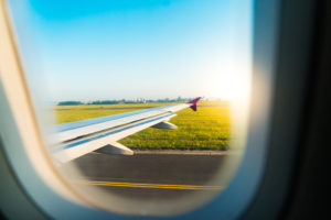 airplane-wing-seen-through-window-during-take-off
